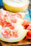 Melon with thin slices of prosciutto Stock Image