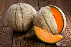 Melon z melonów liśćmi na starym drewnianym stole i plasterkami Organi zdjęcia royalty free