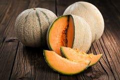 Melon z melonów liśćmi na starym drewnianym stole i plasterkami Organi obraz stock