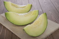 Melone affettato del cantalupo del melone del cantalupo sopra sul tagliere di legno e sul fondo di legno Fotografia Stock Libera da Diritti