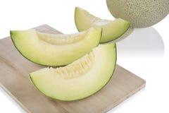 Melone affettato del cantalupo e mezzo melone del cantalupo sopra sul tagliere di legno e sul fondo di legno Fotografie Stock