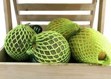 Melone alto vicino proteggere con la rete della schiuma nella scatola di legno fotografia stock