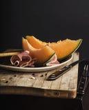 Melone arancio luminoso con il prosciutto di Parma Immagini Stock Libere da Diritti