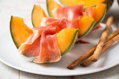 Melone con il prosciutto di Parma e il grissini Fotografia Stock