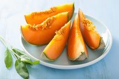 Melone del cantalupo affettato su fondo di legno Fotografia Stock