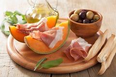 Melone del cantalupo con il prosciutto di Parma e le olive Antipasto italiano Immagine Stock