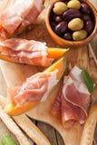 Melone del cantalupo con le olive di grissini di prosciutto di Parma appeti italiano immagini stock libere da diritti