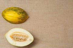 Melone fresco che si trova su una superficie della tela di sacco fotografia stock