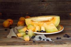 melone fresco delizioso con le pesche ed i mirtilli su un piatto Fotografie Stock Libere da Diritti