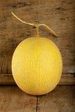 Melone giallo del cantalupo sui precedenti di legno immagini stock