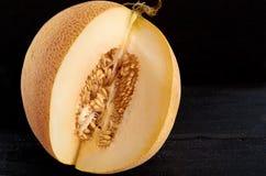 Melone giallo dolce fresco affettato su fondo nero di legno Melone organico crudo sulla fine di legno della superficie di buio su Immagine Stock