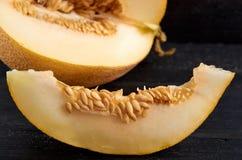 Melone giallo dolce fresco affettato sulla tavola nera di legno Un pezzo di melone organico crudo sulla fine di legno della super Fotografia Stock