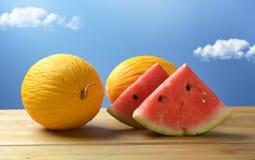 Melone giallo ed anguria rossa sulla tavola di legno con cielo blu dentro Fotografie Stock Libere da Diritti