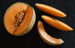 Melone maturo affettato su fondo nero Fotografie Stock Libere da Diritti