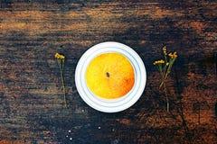 Melone und getrocknete Kamille auf gestreifter Platte Stockfotografie