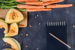 Melone und Karotten auf Schneidebrett Lizenzfreies Stockbild