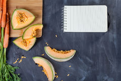 Melone und Karotten auf Schneidebrett Lizenzfreies Stockfoto