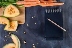 Melone und Karotten auf Schneidebrett Stockfotografie