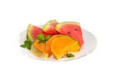 Melonen- und Wassermelonenscheiben auf einer weißen Platte Lizenzfreie Stockfotos