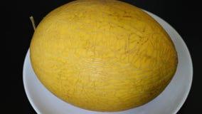 Melonengelb auf einem weißen Teller und einer dunklen Tabelle stock footage