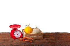 Melones en la caja de madera, fondo blanco Fotografía de archivo libre de regalías