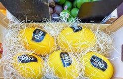 Meloni gialli con gli autoadesivi in scatole di legno da vendere nel segno locale Fotografia Stock