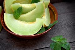 Melonowi plasterki w nieociosanym pucharu, organicznie i soczystego t?ustoszowatym melonie, fotografia royalty free