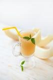 Melonowi smoothies z mennicą na białym drewnianym tle Zdjęcia Stock