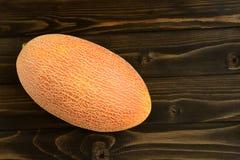 Melons frais sur la vieille table en bois noire photos stock