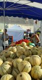 Melons and tomatoes for sale in open air market. Piles of round yellowish greenish Cantelupe type melons and deep shiny red tomatoes for sale on street market stock image