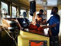 Melsisidorp, Pinkstereneiland/Vanuatu - 9 juli 2016: kapitein van een kleine vrachtboot die de boot over de koraalriffen sturen stock foto