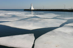 Melspring at the lighthouse. Sheets of ice melt in the harbour Royalty Free Stock Image