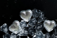 Melt my heart concept with silver wrapped chocolates. And ice cubes, all melting on a dark background Stock Photography