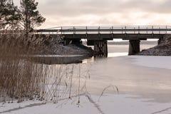 Melt water under bridge at a freezing lake in late autumn. Melt water under a small bridge at a freezing Nordic lake in late autumn stock images