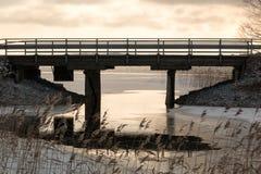 Melt water under a bridge at a freezing lake. Melt water under a small bridge at a freezing Nordic lake in late autumn stock photo