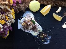 Melt white icecream with lemon on a black tray. White icecream with lemon on a black tray with old dry flowers on a background stock photo