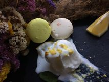 Melt white icecream with lemon on a black tray. White icecream with lemon on a black tray with old dry flowers on a background Royalty Free Stock Image