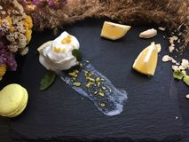 Melt white icecream with lemon on a black tray. White icecream with lemon on a black tray with old dry flowers on a background Royalty Free Stock Photos