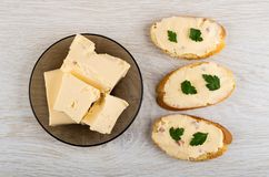 Melted cheese with bacon in plate, sandwiches with cheese and parsley on table. Top view royalty free stock photos