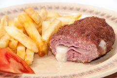 The melted cheese oozes out of stuffed burgers on a plate Royalty Free Stock Image