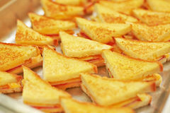 Melted cheese in rosy sandwiches. Wonderful hot sandwiches canapes of triangular shape with cheese and ham, exude wonderful aroma. Their crispy crust like royalty free stock photos