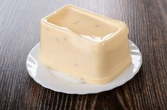 Melted cheese in glass plate on dark table stock images