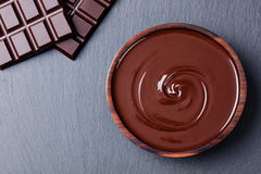 Melted chocolate and bar chocolate. Slate background. Copy space Top view royalty free stock photos