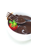 Melted chocolate in a cup, fork and strawberries Royalty Free Stock Images