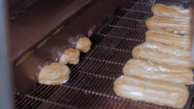 Melted chocolate flowing on fresh creamy eclair cakes on a conveyor at a bakery. stock video footage