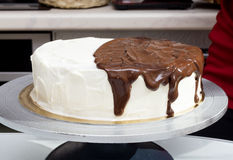Melted chocolate spreads over cream cake Stock Photo