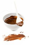 Melted dark chocolate dripping from the spoon. Melted dark chocolate dripping from the wooden spoon stock photo
