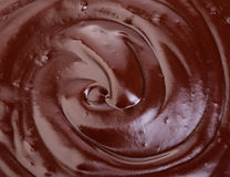 Melted dark chocolate flow, candy or chocolate preparation close-up as a background. Royalty Free Stock Photo