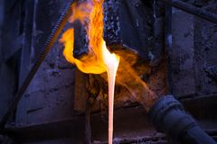 Melted glass furnace in glass factory. The melted glass flows from the furnace stock image