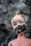 Melted scary girl doll on a ash background Royalty Free Stock Photos